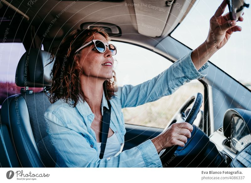 young beautiful woman driving a car and adjusting rear mirror. travel concept sunny sunglasses traveling wheel drive hire sharing new traffic maintenance