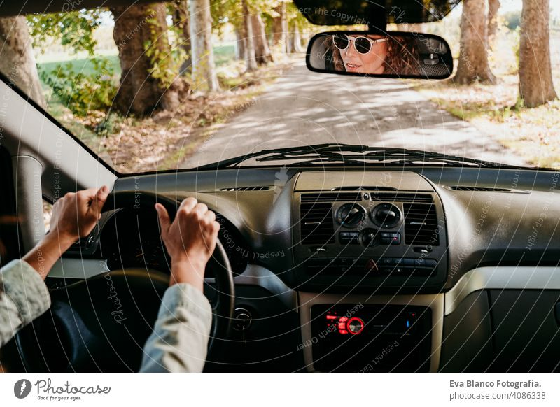 young beautiful woman driving a car. travel concept. view from inside. path of trees road sunny sunglasses traveling wheel drive hire sharing new traffic