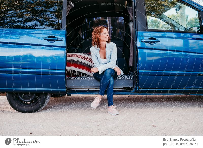 happy woman sitting in a blue van and having fun. travel concept. woman using mobile phone laugh car enjoying outdoors resting camp path way sunset wanderlust
