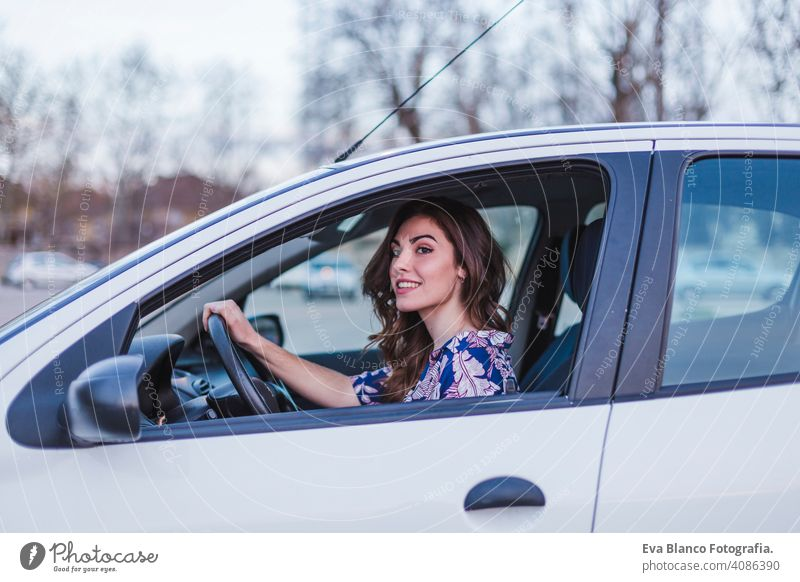 Young woman driving a car in the city. Portrait of a beautiful woman in a car, looking out of the window and smiling. Travel and vacations concepts interior
