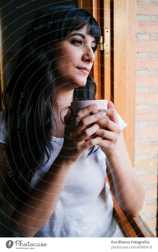 young caucasian woman at home by the window having a cup of coffee or tea. Morning and relax concept. Lifestyle indoors girl comfortable house hotel mug modern