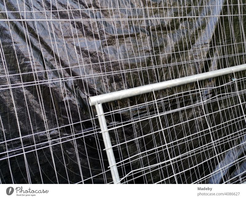 Construction fence with grey wire mesh and black plastic privacy screen on a construction site on the campus of Goethe University in Frankfurt am Main Bockenheim, Hesse