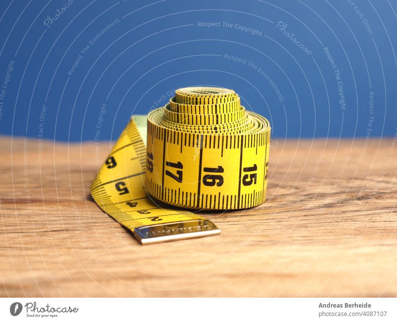 Yellow tailor tape measure on a wooden table, close up precision healthy overweight perfect centimeters professional ideal size concept skill diet designer