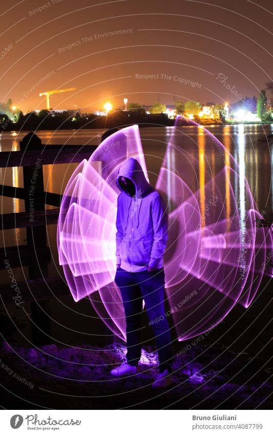 A man standing with his hands in his pockets and a hood over his head, standing at night in front of a lake. Violet abstract shape with light saber behind it. City lights in background.