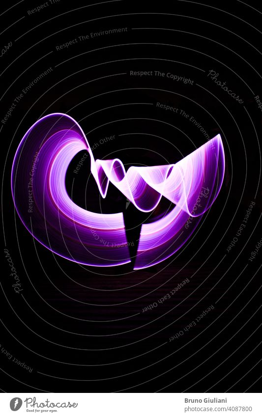 Curved abstract shape made with a light saber violet. Lightpainting session at night. Leds light effect. lightpainting art bright color colorful concept