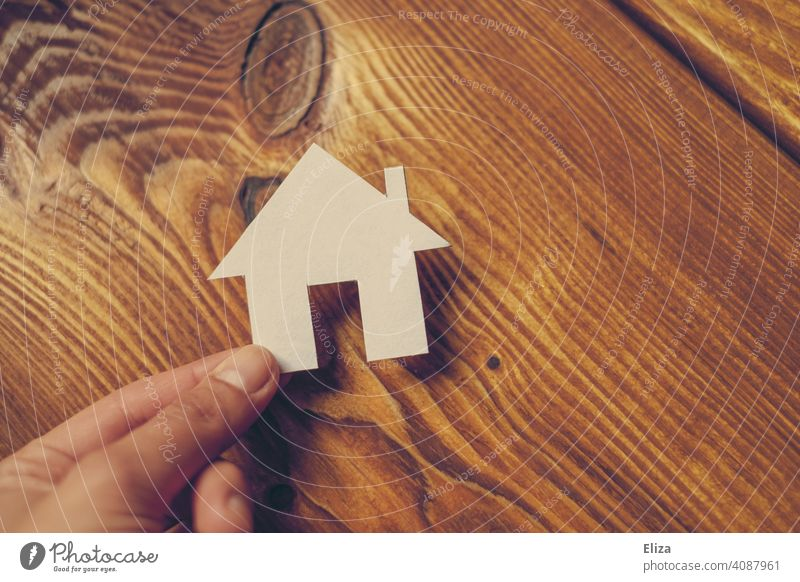 One hand holding a house made of paper. Home and house building. House (Residential Structure) Paper House building at home Dream house Wood build a house Build