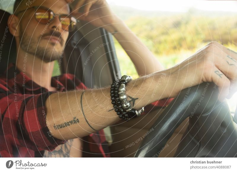 man in car - hand on steering wheel Man portrait car interior sunglasses Car driver arm jewellery Bangle Cool Model Driving 30 years naked torso relaxed Summer