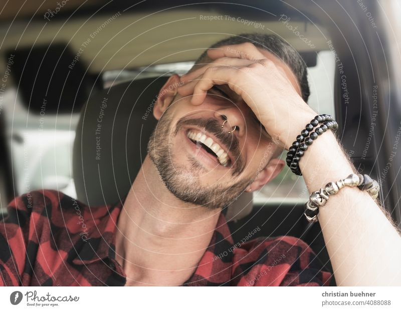 young man sitting in car laughing portrait Man 30 years Hand Bangle Teeth driver's seat happy Positive Sun Fashion vacation holilday relaxed likeable