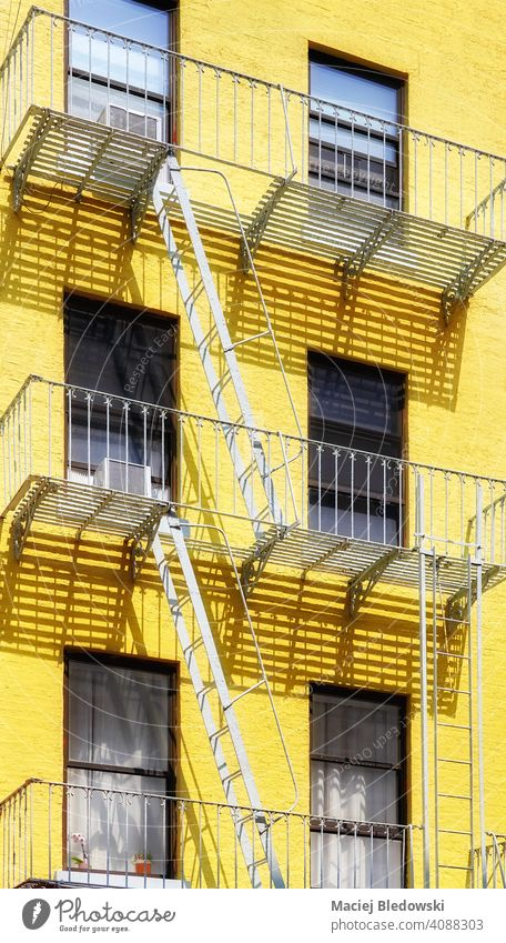 Old yellow building with iron fire escape, New York City, USA. city Manhattan old architecture house facade stairs NYC ladder residential urban America exterior