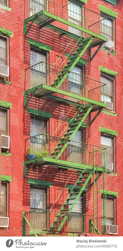 Old red brick building with green iron fire escape, New York City, USA. city Manhattan old architecture stairs house apartment facade NYC ladder residential