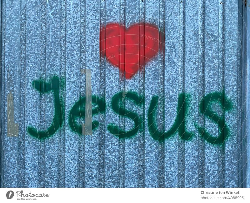 Graffiti with the name Jesus and a red heart on a metal facade Heart Love metal wall Red Easter Holy Week Belief Hope Church Jesus Christ Religion and faith