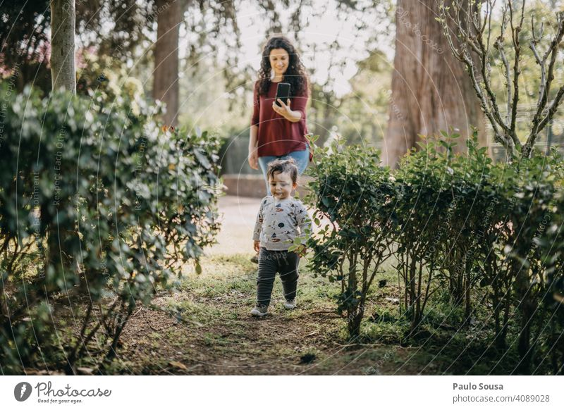 Mother photographing child playing  in the park Mother with child Child Caucasian 1 - 3 years Playing Park having fun Life Parents Love Together Joy Happy