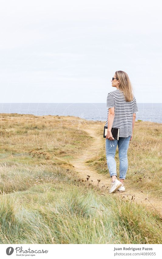 Woman walking along a path in front of the sea holding a book and headphones in her hand read outside relax relaxed enjoy literature mature novel weekend