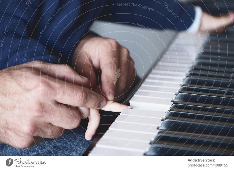 Anonymous father teaching son to play piano hands playing music pushing keyboard lesson home man boy little kid child adult family dad parent together