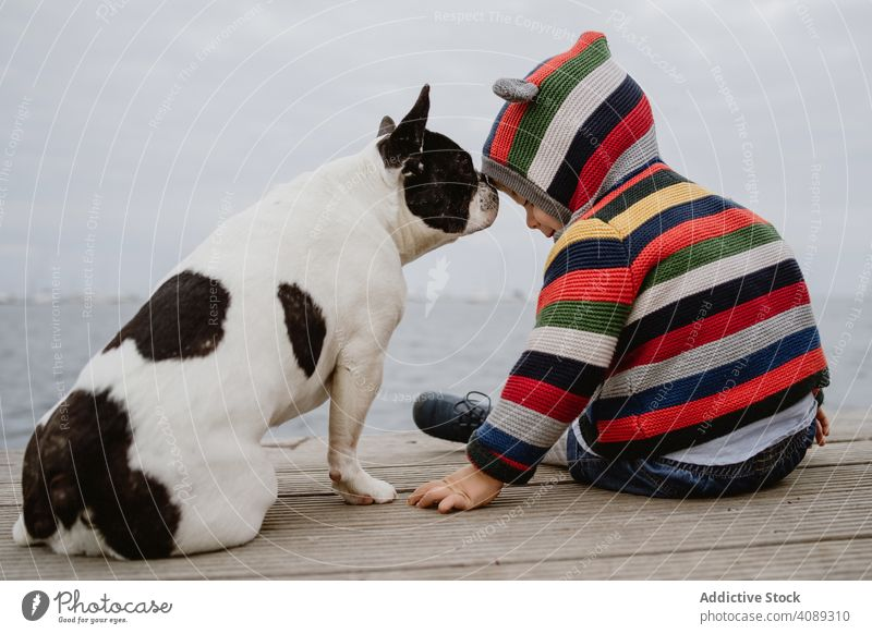 Anonymous kid petting dog on pier patting sea sitting obedient baby french bulldog casual child lifestyle leisure rest relax striped jacket hood puppy loyal