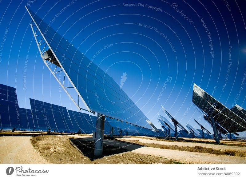 Solar panels against blue sky solar power station reflecting photovoltaic cloudless sunny field cells daytime energy electricity technology shiny weather