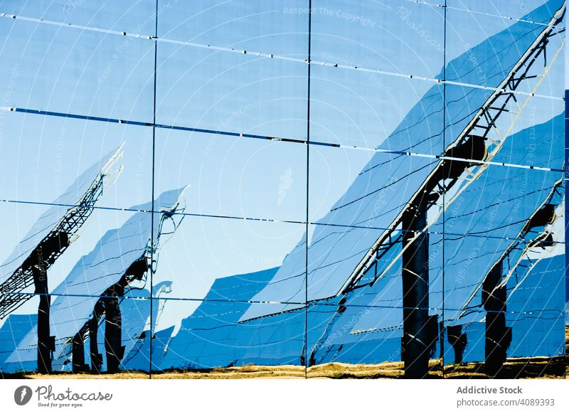 Reflection of solar panels on glass wall power station reflection shiny sunny cells daytime energy electricity technology weather photovoltaic ecology renewable