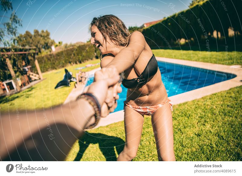 Woman holding of anonymous man woman follow me pool playful cheerful summer vacations carefree couple youth together fun laughing playing recreation tropical