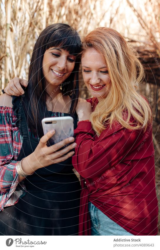 Young women looking in smartphone showing sharing young hugging smiling using browsing mobile female people person holding communication device happy friends
