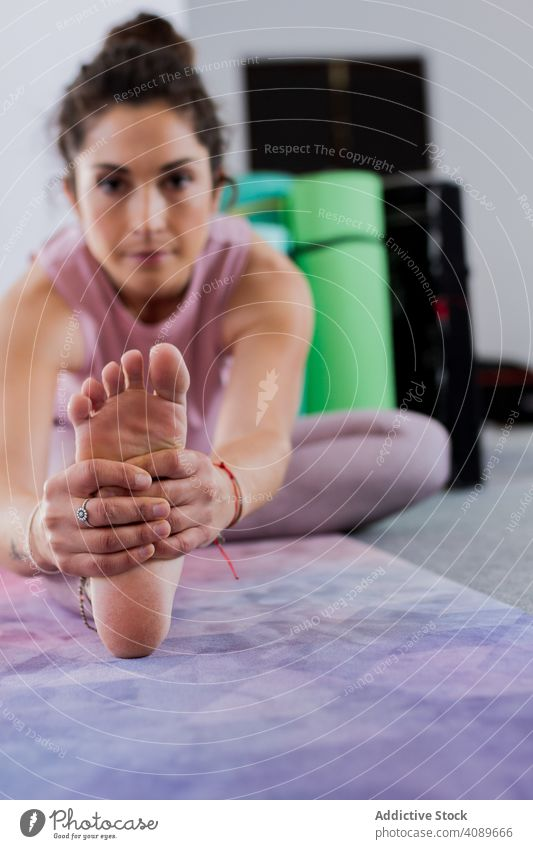 Attractive pensive woman doing yoga indoors concentrated practicing workout stretching attractive flexible sportive pose above head brunette young contemporary