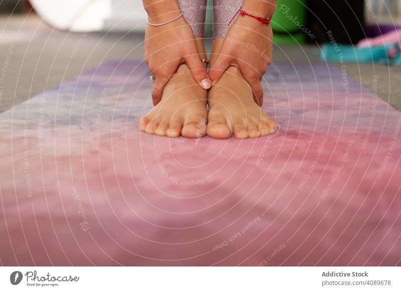 Faceless athletic woman doing standing yoga pose feet hands flexible position pink mat sport relaxation practicing meditation harmony fitness healthy lifestyle