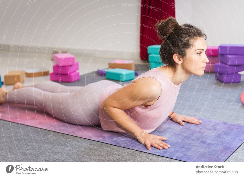 Young attractive woman practicing yoga indoors young flexible sportive concentrated pose lying sportswear brunette relaxation meditation fitness mat healthy