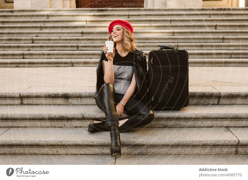 Cheerful tourist drinking on steps woman stairs suitcase smiling looking away joy takeaway stylish female young lifestyle leisure happy cheerful laughing