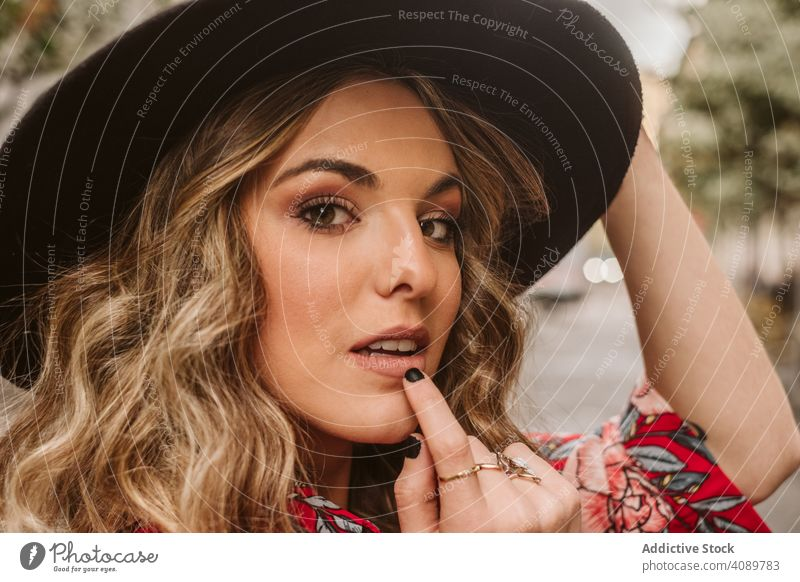 Sensual young woman on street stylish sensual touching lip hat elegant city female model lifestyle leisure summer urban trendy voguish glamour fashion headgear