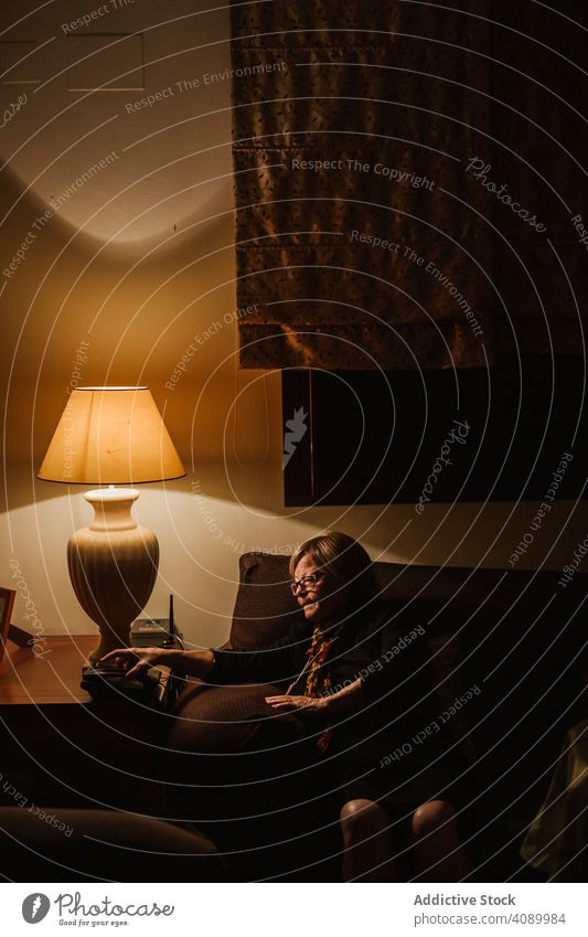 Pleased senior female talking on phone woman glad smiling elderly home dark room evening cozy mature retired pensioner pleasant communication connection call