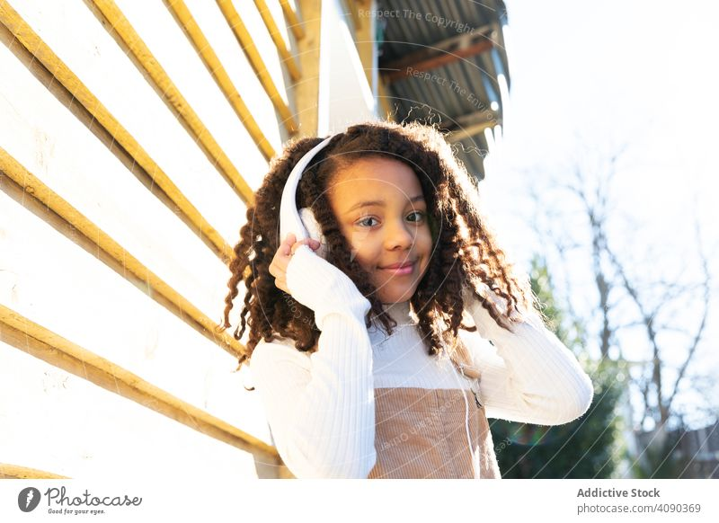 African-American girl listening music with headphones african american black happy young beautiful pretty attractive people lifestyle standing technology