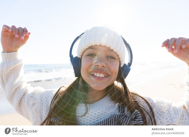 Girl listening to music near sea girl beach smartphone using smiling waves headphones hat casual kid child teen earphones relax rest lifestyle leisure shore