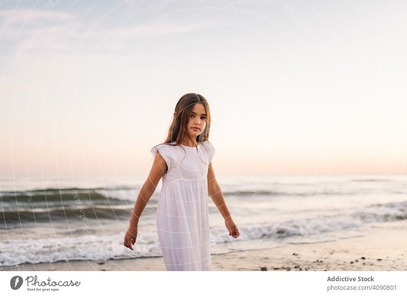 Adorable girl walking and looking at camera on seaside at sunset adorable seashore sunshine beach summer water sunny child childhood happy happiness vacation