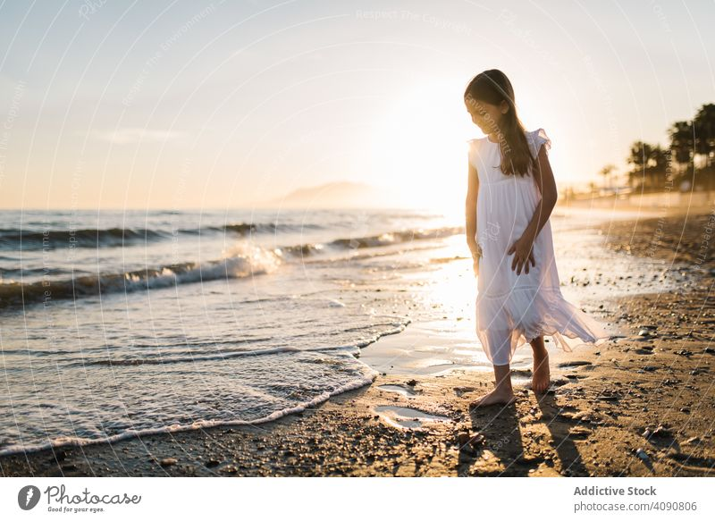 Adorable girl walking and playing on seaside at sunset adorable seashore sunshine beach summer water sunny child childhood happy happiness vacation travel