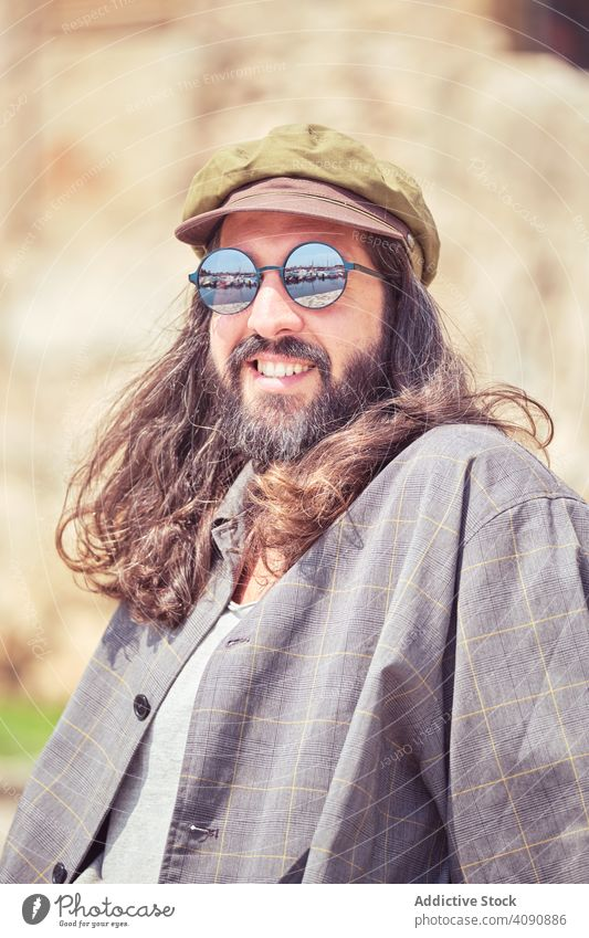 stylish bearded man with long hair sitting on street with sunglasses trendy mustache portrait guy looking cool handsome urban fashionable model attractive