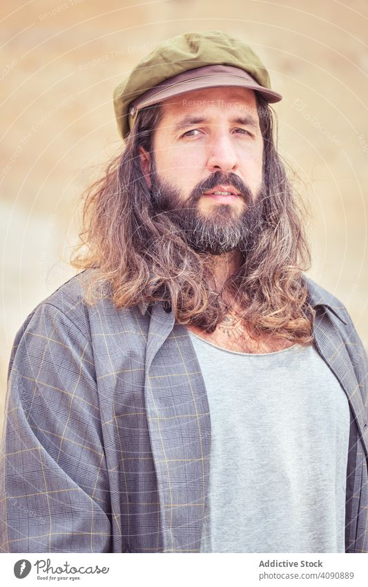 stylish bearded man with long hair on street posing and looking at camera trendy mustache sunglasses portrait guy cool handsome urban fashionable model