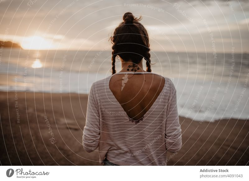 Anonymous female standing towards waving sea on sunset woman beach waves evening young summer vacation ocean water storm nature countryside travel trip tourism