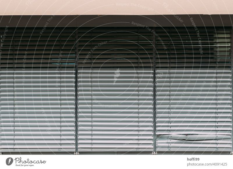 The dented slat of the closed blind. blinds Venetian blinds Broken broken blind Closed Roller blind Shadow Roller shutter Facade Structures and shapes Building