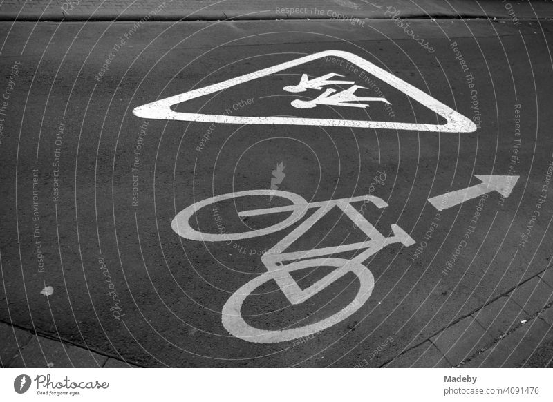 Painted notice for car drivers and cyclists on school children on grey asphalt in the Mathildenviertel in Offenbach am Main in Hesse, photographed in neo-realistic black and white
