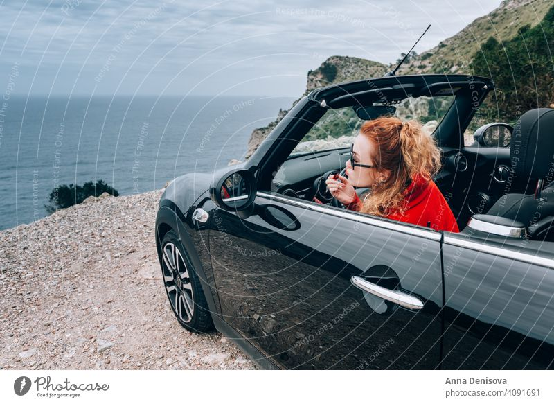 Young woman in cabriolet car convertible young woman in car convertible car gloss lipstick auto happy attractive summer vacation rental lifestyle open roof