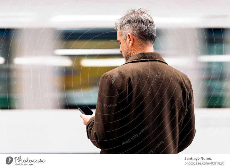 Unrecognizable business man using smartphone in the underground. person lifestyle people middle aged handsome senior caucasian city adult male portrait casual