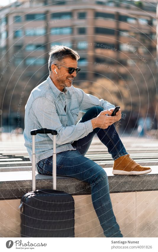 Business man listening to music in the street. person lifestyle people middle aged handsome senior outdoors caucasian city adult male portrait casual urban