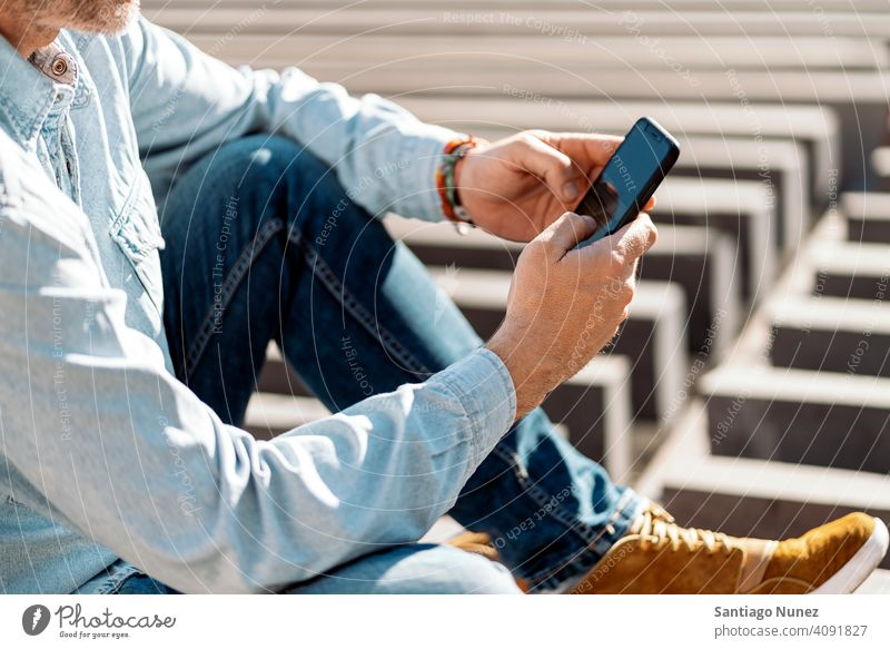 Close up of a business man using his smartphone in the street. person lifestyle people middle aged handsome senior outdoors caucasian city adult male portrait
