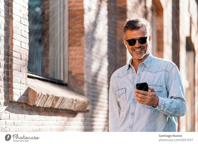 Business man using his smartphone in the street. person lifestyle people middle aged handsome senior outdoors caucasian city adult male portrait casual urban