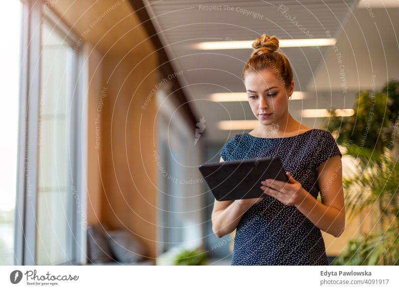 Young businesswoman using digital tablet in her office girl people Entrepreneur successful professional young adult female lifestyle indoors millennial