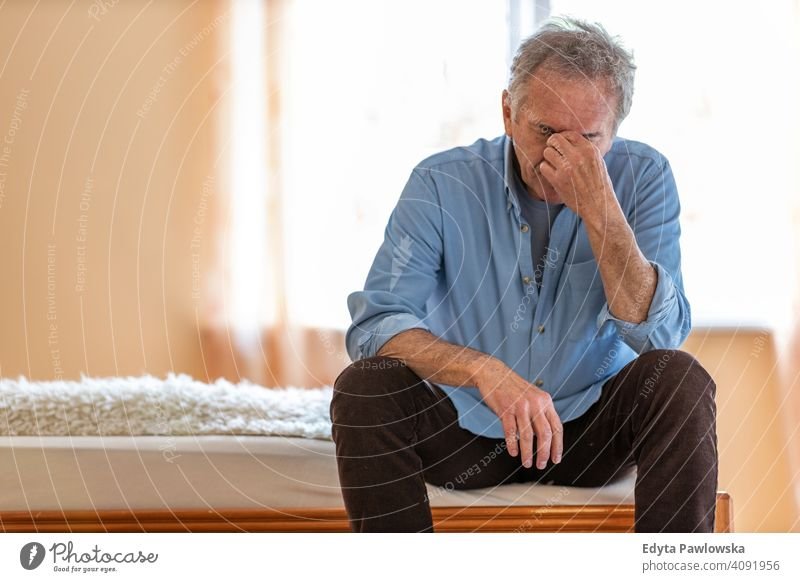Senior man suffering from a headache migraine dementia tired senior elderly grandfather old pensioner retired retirement aged mature home house male people