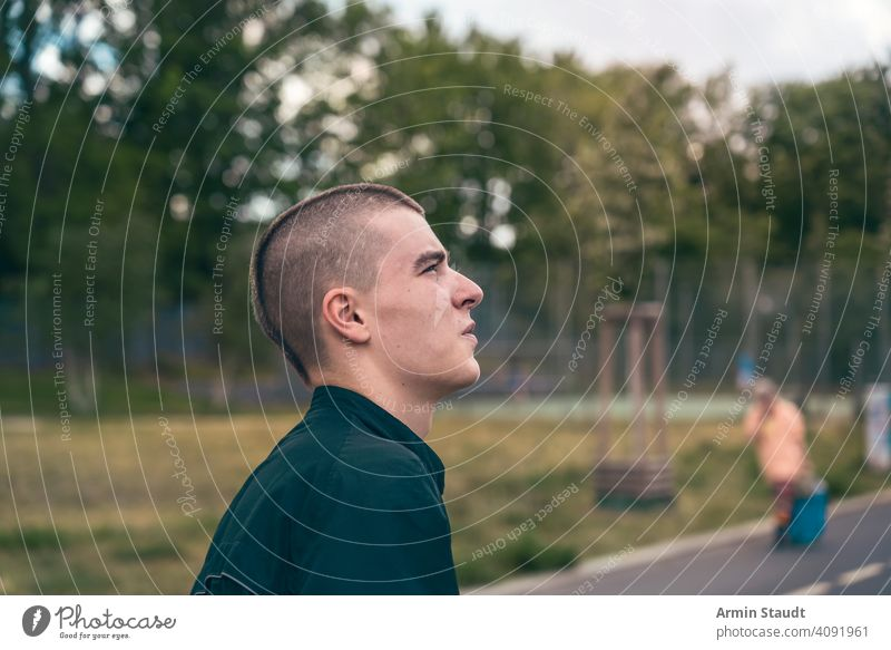 portrait in profile of a serious young man on the street teenager looking male beautiful casual caucasian outdoor confident model lifestyle journey trip travel
