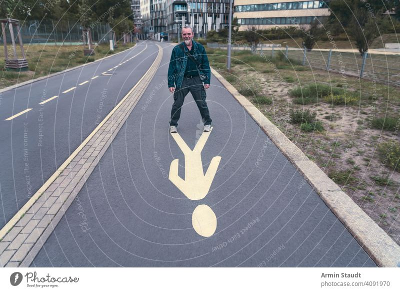 laughing, older man stands on a pedestrian sign street pictogram smile outdoor berlin way road pavement jeans jacket beard senior dynamic vital energy power