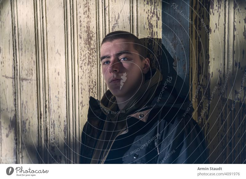 portrait of a serious young man leaning against an old wooden wall paint peeling grunge hoodie cool trendy shadow dark mysterious sunlight powerful confident