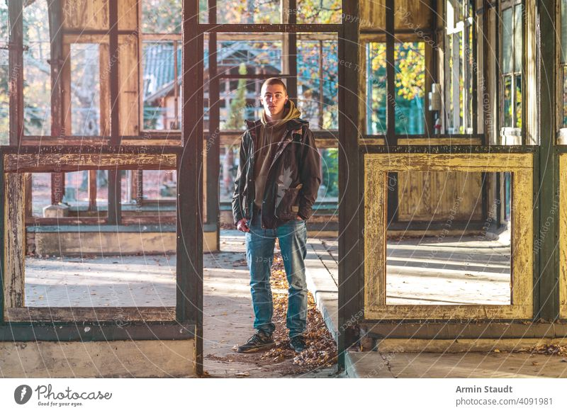 portrait of a smiling young man standing in a ruin house positive smile powerful sunlight evening jacket hoodie beautiful handsome attractive frame construction
