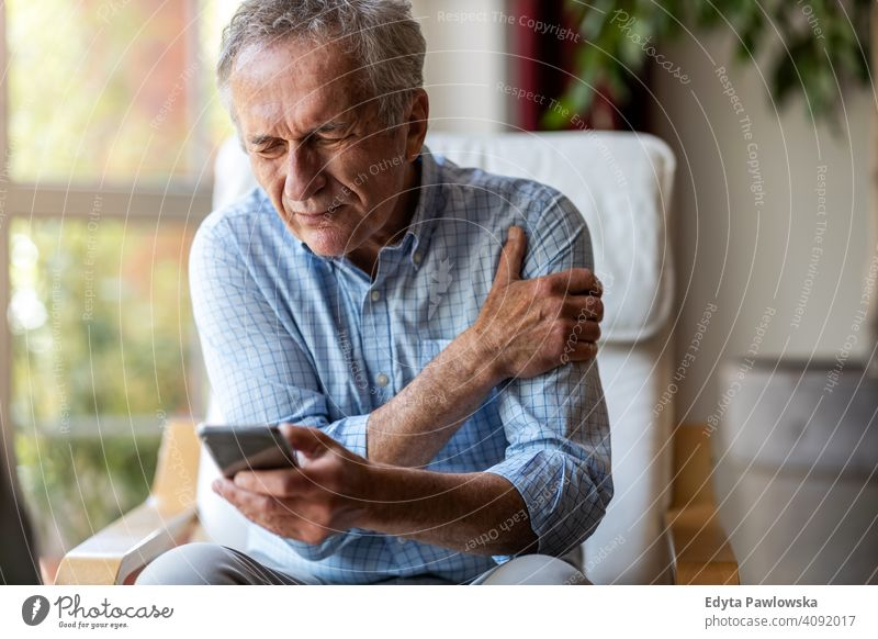 Senior man experiencing pain while using a smartphone at home senior elderly grandfather old pensioner retired retirement aged mature house male people